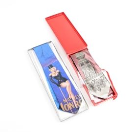 Fornasetti and Ralph Marlin _Marilyn Monroe Technicolor_ Men's Neckties: A pair of men's neckties. Featured is a 1994 Ralph Marlin Marilyn Monroe Technicolor tie with Marilyn Monroe posed in a top hat with a cane on a blue field of Eiffel Tower and star graphics. Also included is a pink silk Fornasetti tie with a grey and white graphic depicting a Corinthian column with a cherub base. The neckwear is presented in the original boxes.