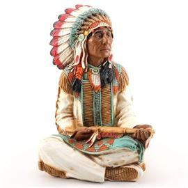"""Universal Statuary Figurine of Native American Man: A Universal Statuary resin figurine of a seated Native American man. He wears a feathered headdress and holds a pipe. The statuette is marked with a monogram and """"Universal Statuary 1980"""". There is also a faded sticker on the underside that reads """"Trees of Mystery…California""""."""
