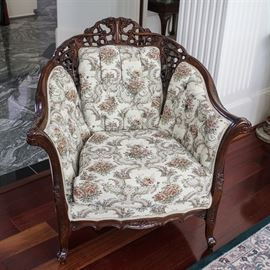 """Vintage Queen Anne Style Upholstered Arm Chair by Kimball: A vintage Queen Anne style upholstered arm chair by Kimball. This mahogany frame chair features a curved crest rail with pierced C-scroll and floral motif. The chair features sloping armrests flanking button tufted back and side panels. The chair includes a removable seat cushion over a scalloped and pierced apron rising on acanthus leaf carved cabriole legs terminating on whorl feet. The chair is upholstered in an off white fabric with a floral design. It is marked """"Kimball"""" under the removable seat cushion."""