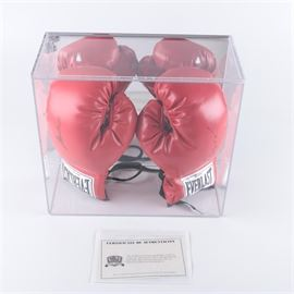 Muhammad Ali and Sugar Ray Leonard Signed Boxing Gloves: A pair of signed boxing gloves from Muhammad Ali and Sugar Ray Leonard. These red-tone Everlast brand gloves are marked to the sides in black-tone permanent ink signatures, and housed in a hard plastic display case. The plastic case locks and comes with a key. The gloves come with a certificate of authenticity from Classic Moments.