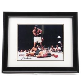 Autographed Muhammad Ali Photograph: An autographed Muhammad Ali Photograph depicting the iconic fight between Muhammad Ali vs. Sonny Liston in 1965. The photograph is autographed by Muhammad Ali in black ink to the bottom left. The images is set in a white mat and is presented behind glass in a black frame.