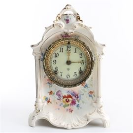 Victorian Style Royal Bonn Porcelain Case Mantel Clock: A Victorian Style Royal Bonn porcelain case mantel clock. This clock features a white porcelain case with with hand painted pansies, and floral motifs with gilt accents with ornate embellishments. The ivory clock face features black Arabic numbers, brass toned hands, and ornate brass bezel that opens on a hinge. The verso is open, and offers a set of three keys.