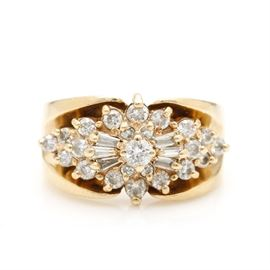 14K Yellow Gold Diamond Cluster Ring: A 14K yellow gold 0.68 ctw diamond cluster ring. This ring features center clustered step diamonds within a marquise shaped body affixed to a high polish tapered shank.