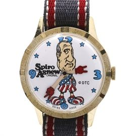 Spiro Agnew Original Wristwatch: A Spiro Agnew original wristwatch. This watch features a nylon red and gray striped strap, which is attached to a round gold tone case that houses a white dial. The image of Spiro Agnew is at the center of the dial and the hour hands are flesh color with red gloves with a black seconds hand. Blue Arabic numerals and blue stars mark the hour indexes.