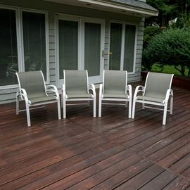 Brown Jordan Patio Armchair Set: A set of four Brown Jordan patio armchairs. The chairs features painted white metal framing with taupe-colored woven vinyl seating. Matches a patio lounge chair by Brown Jordan sold separately in the sale as item 17BOS141-164.