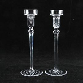 """Rogaska Crystal Candle Holders: A pair of Rogaska crystal candle holders. The candle holders are clear crystal with a tulip shaped holder displaying vertical cuts and rolled edges. Other features of the pair are a brilliant cut orb neck and a faceted stem that tapers to a circular base with an etched sunburst design. The candle holders are labeled """"Rogaska"""" to the underside."""
