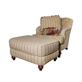 Upholstered Arm Chair with Ottoman, Accent Pillows, and Throw: An upholstered arm chair with ottoman, accent pillows, and throw. This set includes a chair with curved crest rail and button tufted back with cushioned arm rests flanking a seat cushion over a shallow apron rising on turned and tapered feet. Also includes a rectangular, cushion top ottoman rising on wooden feet. The two accent pillows are upholstered in a striped fabric matching the ottoman and complimenting the floral patterned chair upholstery. Includes a colorful throw with tassel ends. There are no visible maker's marks.