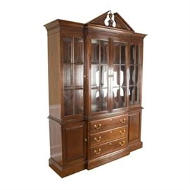 Ethan Allen Chippendale Style Breakfront China Cabinet: An Ethan Allen Chippendale style breakfront china cabinet. This cabinet features: a broken pediment with an urn style finial, wide molding with dentil detail, two doors on the upper section of the breakfront and single doors to either side all with two-over-three paned glass, three stacked drawers on the lower section of the breakfront with single paneled cabinet doors to either side, and a wide molding with a graduated edge. The sides are solid panels on both the upper and lower sections. Brass tone hardware on the drawers and doors accents the dark tone wood. Companions 17BAL110-133;17BAL110-135.