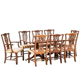 Mahogany Dining Table and Eight Chippendale Style Chairs: A mahogany dining table with two wide leaves and eight Chippendale style chairs. The table and leaves feature cross-banded borders. The top has rounded corners, supported on double-pedestals, each with a turned pedestal and three splayed legs with string-inlay and brass capped feet and casters. The two arm and six side chairs having pierced-carved splats, over satin striped, upholstered seats, over reeded Marlborough front legs. Includes custom pads.
