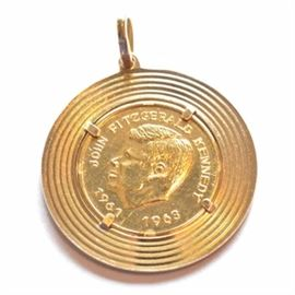 21K Yellow Gold John Fitzgerald Kennedy Coin Pendant: A 21K yellow gold John F. Kennedy coin necklace pendant, dated 1961-1963, in an 18K gold enclosure.