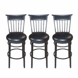 Three Swivel Bar Stools: A set of three swivel bar stools. The stools are presented in a black intentionally distressed finish and feature metal frames with slatted backs and padded vinyl seating.