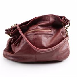 Cuore & Pelle Leather Shoulder Bag: A leather shoulder bag by Cuore & Pelle. This bag showcases a deep red grained leather exterior with gold tone hardware. It features a fabric lining and is labeled with a brand marking.
