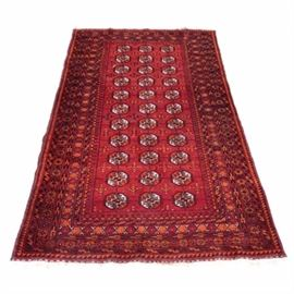 Hand-Knotted Bokhara Area Rug: A hand-knotted Bokhara area rug. The rug features a deep red field with all-over octagonal Tekke style medallions in a palette of red, off-white, and black. The field is enclosed by a compound border that features a double cross pattern along the inner border and an abstract geometric pattern along the primary border. The rug has an overcast edge with a short wool fringe to either end. Unmarked.