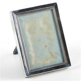 """Lunt Sterling Silver Picture Frame: A Lunt sterling silver picture frame. The picture frame features a rectangular shape with beveled line detail around the interior of the frame. The backing of the frame is lined in a blue fabric material. The piece is marked, """"Lunt Sterling,"""" to the bottom of the frame. The total approximate weight excluding the non-silver components is 0.400 ozt."""