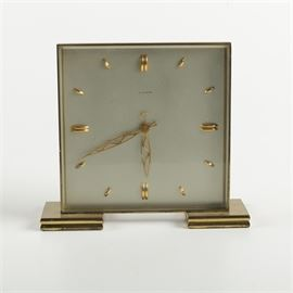 """Vintage William Barthman Square Desk Clock: A vintage metal desk clock. A square gold tone metal desk clock with an off-white face and marked above the gold tone, openwork hands """"William Barthman"""", resting on two square platform feet."""