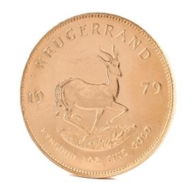 """1979 South African 1 Ounce Fine Gold Krugerrand Coin: A 1979 South African 1 ounce fine gold Krugerrand. This coin, minted by the South African Mint and 32.80 mm in diameter, features the likeness of Paul Kruger, South Africa's first president, along with """"South Africa"""" in Afrikaans and English to obverse. The reverse displays the year of minting and gold weight along with the image of the national animal of South Africa, a Springbok antelope."""