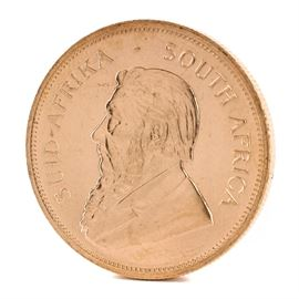 """1979 South African 1 Ounce Fine Gold Krugerrand Coin: A 1979 South African 1 ounce fine gold Krugerrand. This coin, minted by the South African Mint and 32.8 mm in diameter, features the likeness of Paul Kruger, South Africa's first president, along with """"South Africa"""" in Afrikaans and English to obverse. The reverse displays the year of minting and gold weight along with the image of the national animal of South Africa, a Springbok antelope."""