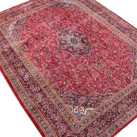 Semi-Antique Persian Mashad Room Size Rug: A semi-antique hand-knotted Persian Mashad room size rug. This wool constructed rug features a navy, ivory, olive, and scarlet central medallion flanked by two pendants on a decorated scarlet field. The rug has a compound border in a coordinating color scheme and two natural warp fringed ends.