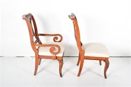 Eight Cherry and Upholstered Dining Chairs: A set of eight cherry dining chairs with upholstered seats. The chairs feature arched top rails with a carved accent, back rests with oval, bead trimmed openings set inside three scrolled braces. The set included two captain's chairs with scrolled arms, The chairs stand on cabriole front legs and saber back legs. The chairs are upholstered in tone on tone cream colored, machine embroidered fabric with matching trim. Companion dining table under 17LEX185-095, sideboard 17LEX185-092, and two-piece hutch 17LEX185-096