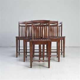 Six Tall Walnut Dining Chairs: A set of six walnut tall chairs with arched top rails and slatted backs. The seats are contoured for comfort and the chairs stand on four tapered legs, with a box stretchers. The front stretchers are fitted with transparent, plastic guards to protect from scuffs when used as a footrest. Companion table listed under 17LEX185-103.