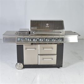 Jenn-Air Outdoor Gas Grill: The model:number 720-0709 A Jenn-Air outdoor propane grill. The steel grill has an igniter and seven fire temperature dial controls to the front panel. The grill area is flanked with stainless steel shelves, with two warming drawers beneath and a hinged door with a place for the propane tank. The hinged, lift-up top is fitted with a bar handle that extends across the front of the lid with a temperature gauge. The unit sits on caster feet for portability. Untested. The model:number 720-0709.