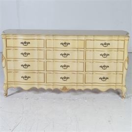 French Provincial Styled Dresser: A French Provincial styled dresser featuring a total of nine drawers in a horizontal format, three set of equal sized drawers. The center top drawer is divided . The chest is finished in a cream color with grooved line details painted in dark gold and stands on cabriole legs. The case has brass tone hardware, faux escutcheons and decorative carving. Companion chest of drawers listed under 17LEX185-077