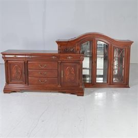 Two-Piece Cherry Veneered Hutch: A two piece cherry veneered hutch. The illuminated top section features an arched top with arched center doors accented with wood beading and metal hardware. Flanking the center doors are two side doors with reversed arched tops and and oval wood design on the side glass. two half columns, mirrored back with fixed glass shelves. The bottom features three felt bottomed drawers, three center drawers flanked by two hinged cabinet doors embellished with oval and arched wood. The doors are also accented with beaded trim and side columns. The piece stands on bracket feet. Companion dining table listed under 17LEX185-095, sideboard 17LEX185-092, and chairs 17LEX185-078.
