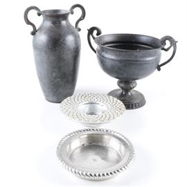 Metal and Glass Home Decor: A selection of metal and glass home decor. The selection includes four pieces such as a metal footed bowl with a black finish, scrolled side handles and the bowl stands on a pedestal with a round base that is accented with dentil moulding. Other features of the selection include an urn style vase with a black finish and scrolled side handles, a faux pearl rimmed metal bowl and a silver tone metal bowl with a rope twist style edge.