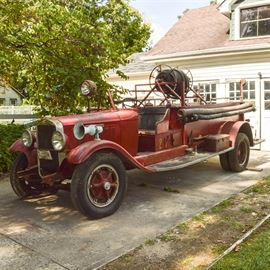 1929 Studebaker Fire Engine: An historic 1929 Studebaker model S 60 fire engine; serial number is 3476638 and odometer reads 06097, with a red frame, historic license tags, wooden running boards, a spotlight and siren, an attached tool box, an axe, three brass firehose nozzles, a wooden ladder, and reeled hose. This engine was originally owned by the city of Sadieville, Kentucky.
