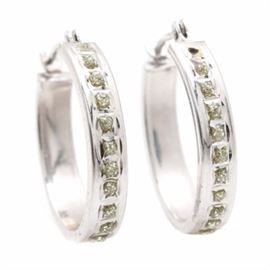 14K White Gold White Sapphire Earrings: A pair of 14K white gold white sapphire earrings. These earrings showcase a faceted round white sapphire and the rest of the settings set with glitter resin minus one.