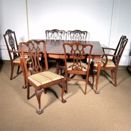 """Chippendale Style Dining Table and Chairs: A Chippendale style dining table and six chairs with a mahogany veneer. The table has a rectangular top, a scalloped apron with cross-hatched accents, and cabriole legs with ball-and-claw feet; it features a central support to the underside consisting of two tapered legs terminating in bun feet. Each chair features a pierced splat back and a cushioned seat upholstered in red, green, and yellow plaid fabric; two chairs have bowed arms with scrolled handholds. The chairs rest upon cabriole legs with carved acanthus leaves to the knees and ball-and-claw feet. They are marked """"No. 715 S. Mah Palona Wine Gray"""" to their undersides."""