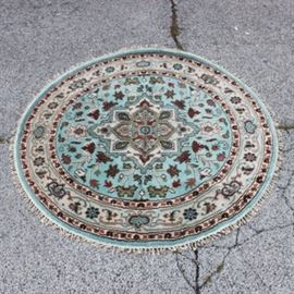 Contemporary Hand-Knotted Indo-Heriz Round Wool Area Rug: A hand-knotted Indo-Heriz round wool area rug. This rug features a pale turquoise field with a star central medallion, surrounded by herati patterns with an ivory turtle border. The colors shown through out this rug are red, rose, deep indigo, greens, dark brown, and blues, and finished with an overcast selvedge edge, and natural warp double knotted fringe. Unmarked.