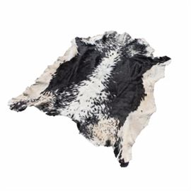 Contemporary Calf Hide Accent Rug: A calf hide accent rug. This hide features black and white coloring to the fur with a natural cut edge, and a suede backing. This rug goes unmarked.