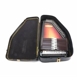 Chromaharp 15-Chord Autoharp and Case: A fifteen-chord ChromAharp autoharp with tobacco burst finish; chord bars provide the primary chords of seven keys. Chords include Eb, D, F7, Gm, Bb, A7, C7, Dm, F, E7, G7, Am, C, D7 and G. A black chipboard style case is included.