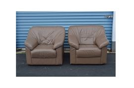 Pair of Bonded Leather Club Chairs: A pair of bonded leather club chairs. Each chair features a pillowed design with straight crest sloping to angled arms with panel sides and flat apron front. The chairs are upholstered in a tan tone bonded leather and include quilted accent on the seat back.