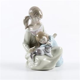 "Lladró​​ ""Little Sister"" Figurine: A Lladró​​ Little Sister figurine. The older sister looks down at the younger girl, sleeping in her lap with a dozing cat. The piece is marked to the bottom with the hallmark and ""'Lladró​​- Hand Made In Spain – Daisa 1987"" and the model number ""1534"". This model was retired in 2005."