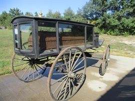 Classic horse drawn funeral carriage with wicker basket