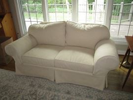 There are two matching 2 seater couches, that have slip covers on them.  The original white upholstery has never been sat on, so they are like new