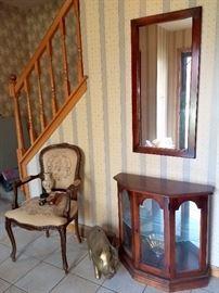 Accent chair. Brass piggy bank. Curio cabinet