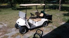 EZ-go golf cart with storage bed on back.