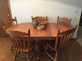 Beautiful condition.  Solid Oak pedestal table with leaf in and chairs.