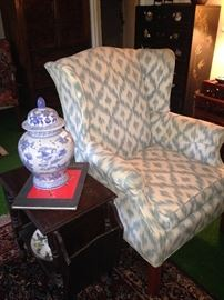 Wingback chair, ginger jar, and side table
