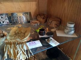 Assorted Native American crafts, including pottery, baskets, minature horsehair baskets and doeskin art