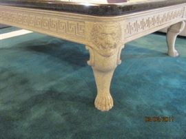 """Brown marble like 45""""x5' coffee table with ivory tone carved lions heads and paws"""