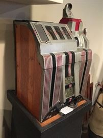 Vintage 1930s Mills nickel slot machine. Working condition with keys and stand.