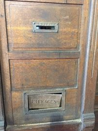 Brass mail slots on antique post office doors.