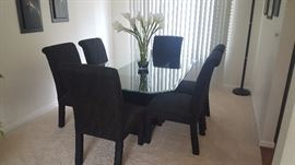 Rectangle beveled glass dining table with six black fabric rolled back parsons chairs.  Perfect condition.