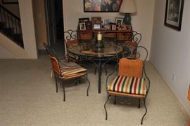 Dining table with glass top, wicker and wrought iron chairs