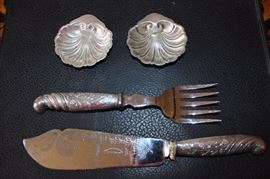 Sterling silver serving knife and fork and two small sterling dishes.