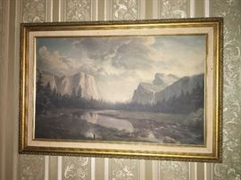 beautiful painting of mountains with gold quilt frame and white linen